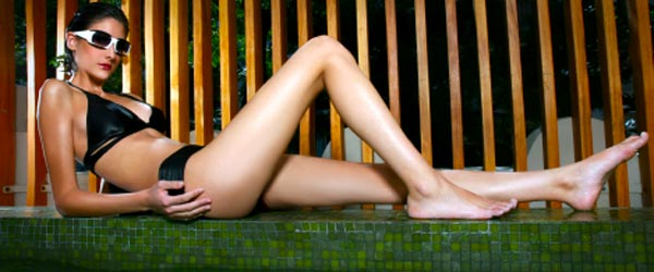 An Argentinean model with legs for days reclines next to a pool.