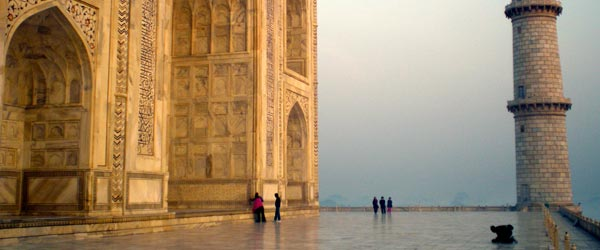 A man praying in front of the Taj Mahal at sunrise.