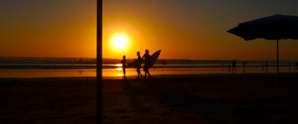 Surfers on the beach at Kuta during the sunset.