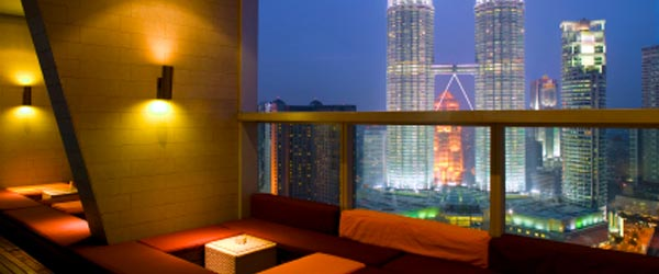 A hotel lounge bar with a view of the Petronas Twin Towers.