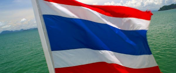 A Thai flag waving in the wind behind a boat off the coast of Phuket.