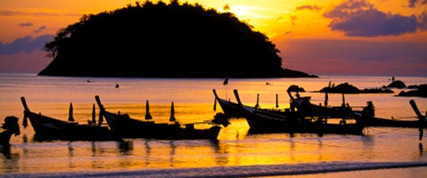 Traditional Thai longboats resting on Kata Beach during the sunset.