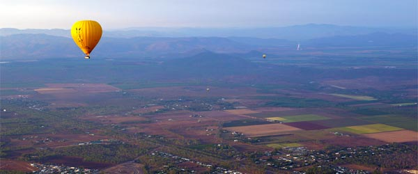 Hot air balloons floating over the rural landscape of Cairns.