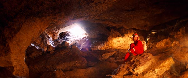 A woman caving or spelunking in an Albertan cave.