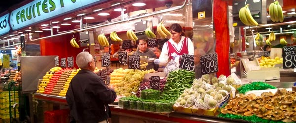 A man buying fruit at a typical stall in the La Boqueria fruit market.