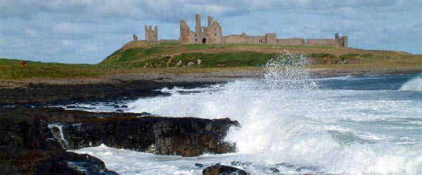 Waves crash on the shore with Dunstanburgh Castle in the background.