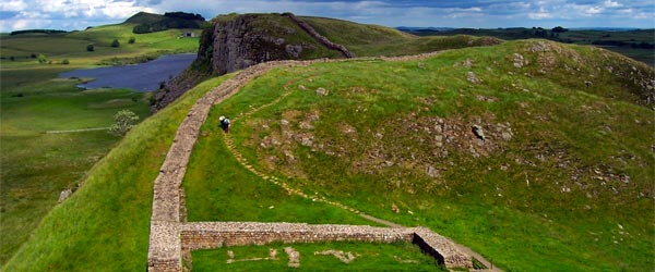 Two hikers walk past a milecastle on Hadrian's Wall.