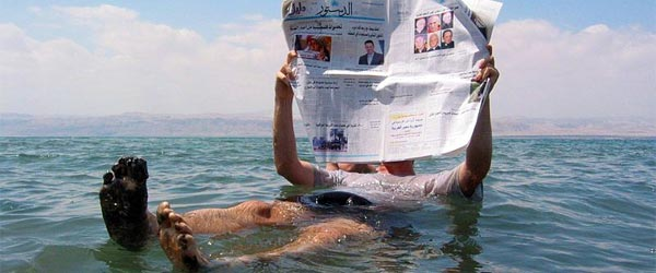 A man floating in the Dead Sea and reading a newspaper.