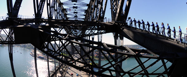 The steel arches of the Sydney Harbour Bridge with traffic racing below.