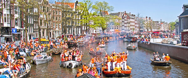 The riotous Queen's Day celebrations in Amsterdam with revelers and party boats.