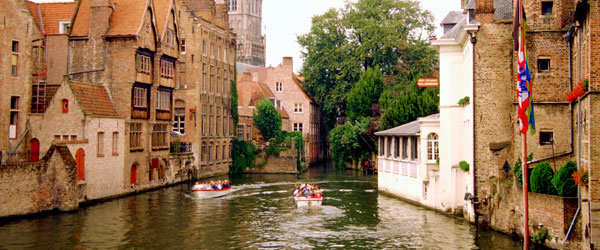 Boats sailing on the river in the center of Bruges surrounded by medieval-era architecture.