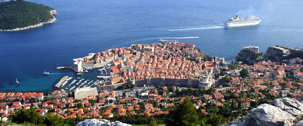A cruise ship sailing by the walled city of Old Dubrovnik on the Croatian coast.