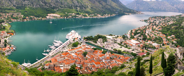 A cruise ship pulling out of the city of Kotor and into the Bay of Kotor.