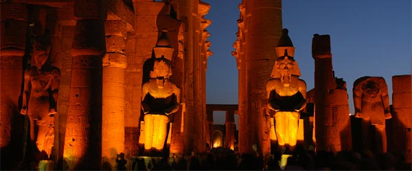The Luxor Temple and its giant statues of pharaohs illuminated at night.