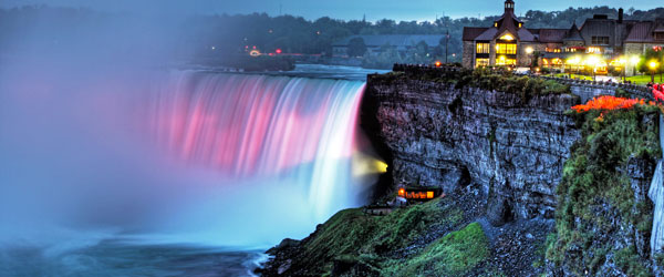 The waterfalls of Niagara Falls are illuminated at night in a bright and mesmerizing display.