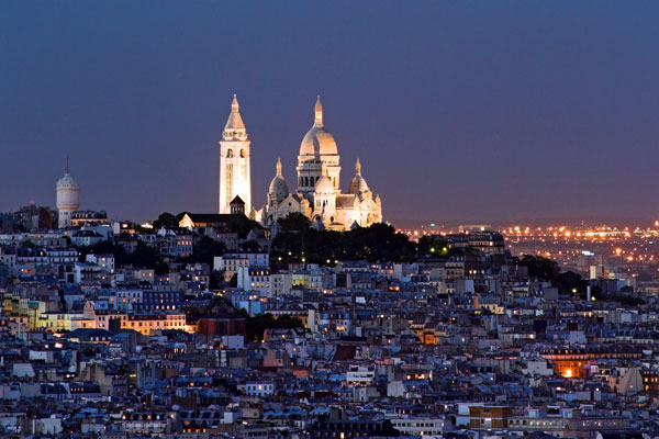 The Sacre Coeur and the neighborhood of Montmartre at night.