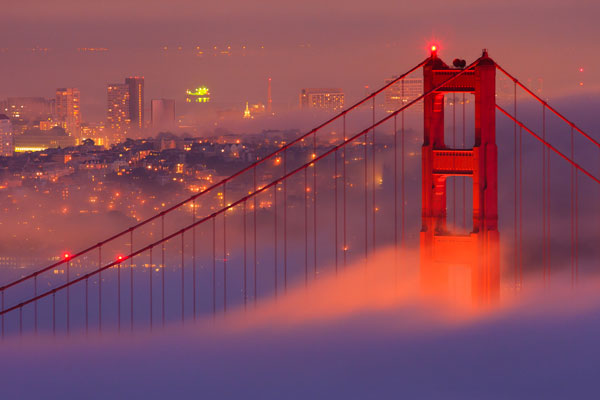 The Golden Gate Bridge and San Francisco just visible through the fog.