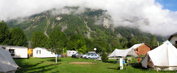 A campground in the French Alps with a mix of tents and mobile homes for rent.
