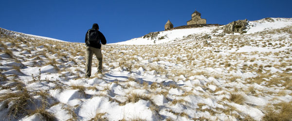 A hiker makes his way up the snowy mountain to the Gergeti Trinity Church in the Republic of Georgia.