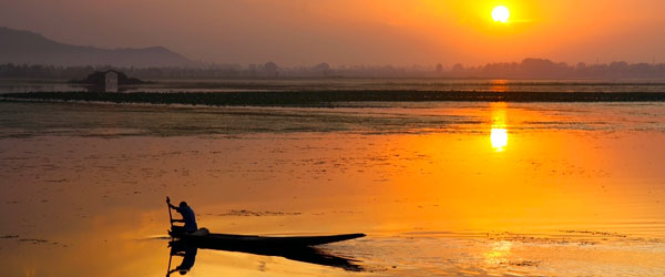 A sunset over Dal Lake and the Himalayas as a local Kashmiri fishermen finishes his day.