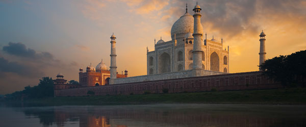 The Taj Mahal at sunrise as seen from the Mentab Bagh Gardens across the river.