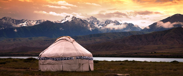 A solitary yurt on the steppes of Kyrgyzstan with the Tian Shan Mountain Range in the background.