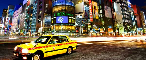 A Tokyo taxi driving through the neon-lit streets of Tokyo.