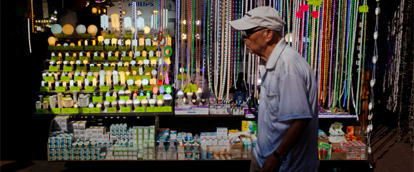 An old man walking past a stall on Apliu Street. Photo credit Chris Brown.
